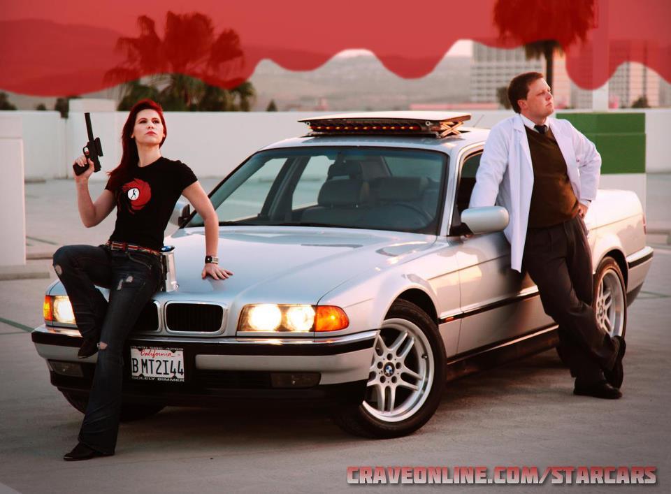 Brian as Q rocking the Tomorrow Never Dies BMW